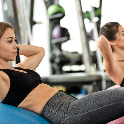 Two cute girls doing heavy athletic workout in the gym doing exercises for abdominal muscles
